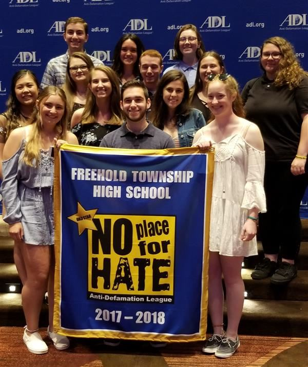 students pose with no place for hate banner