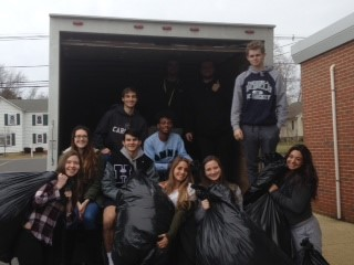 Howell students load coats onto the truck