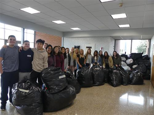 Students pose with all the coats they collected