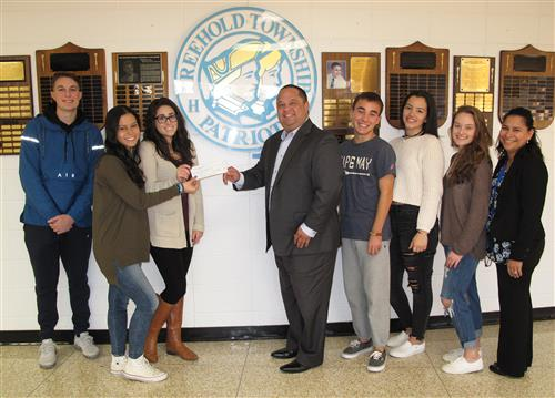 Spanish Club students and teacher deliver check to Catholic Charities representative