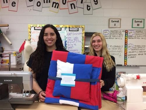 Students show their quilts and blankets