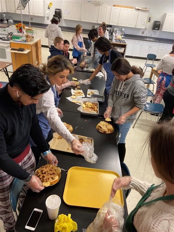 students prepare plates of cookies