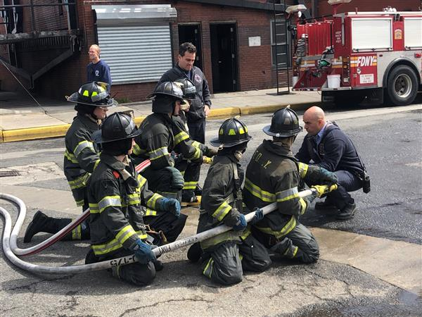 students train at fire academy on how to use a hose