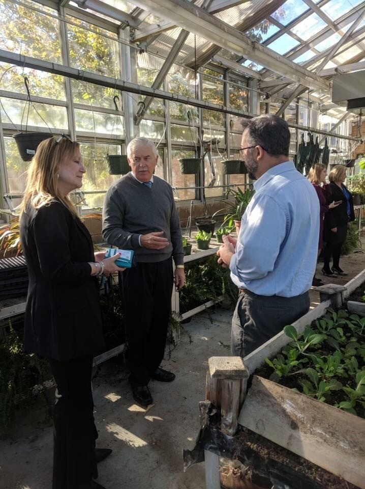 Assemblyman Eric Houghtaling and Assemblywoman Joann Downey speak with a teacher in the greenhouse
